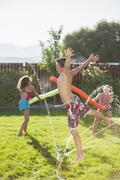 Caucasian children playing in the sprinkler Stock Photos