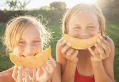 Caucasian girls eating cantaloupe Stock Photos