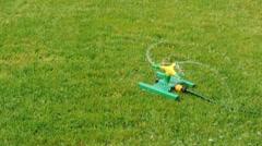 Lawn sprinkler splashing water over green grass. Stock Footage