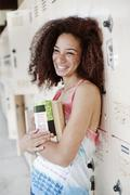 Mixed race woman leaning on school lockers Stock Photos
