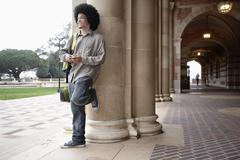Student with afro leaning against pillar on campus Stock Photos