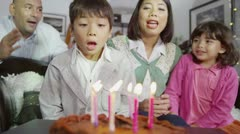 Happy family enjoying a Birthday celebration for young son - stock footage