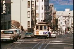 San Francisco, 1970's, Cable Car, coming up hill surrounded by cars - stock footage