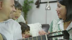 Happy family singing together with father playing the guitar Stock Footage