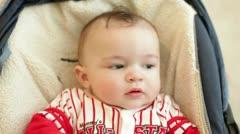 baby carseat rubs eyes - stock footage