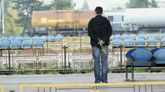 Patient man with a bouquet of flowers waiting the train in the station Stock Footage