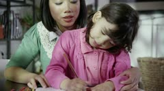 Mother spends time with her daughter, writing and colouring Stock Footage