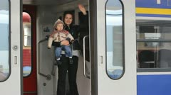 Young mother with her baby standing in a train and saying good bye - stock footage