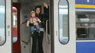 Stock Video Footage of Young mother with her baby standing in a train and saying good bye