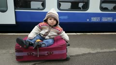 Sweet baby sitting on a suitcase in railway station Stock Footage