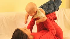 Young mother layed down raising up her baby having fun Stock Footage