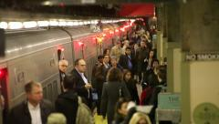 Morning commute crowd of businessmen and women get off a train slow motion Stock Footage
