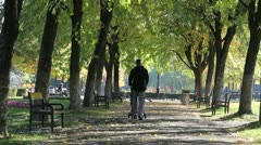 Young man walking in the park with his baby in a baby buggy - stock footage