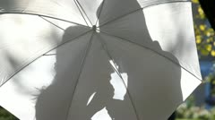 Shadows of two lovers behind the umbrella Stock Footage