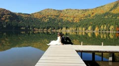 Lovely moments with young married couple after their wedding sitting on dock - stock footage