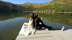 Just married couple sitting on mountain lake dock - stock footage