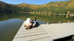 Lovely young married couple laying down on lake dock ang playing with the hands - stock footage