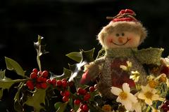 christmas, snowman on a branch of holly - stock photo