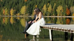 Just married couple sitting on lake dock and enjoying time spent together - stock footage