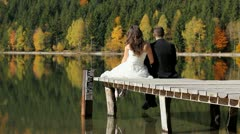 Engaged couple sitting on mountain lake pontoon and admiring the nature - stock footage