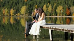 Just married couple on the pontoon, groom talking on the phone and bride waiting - stock footage