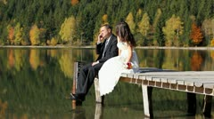 Just married couple, groom talking on the phone, bride admiring the nature - stock footage