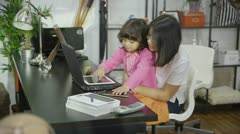 Mother and father helping their children to learn at home with computers Stock Footage