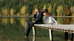 Just married couple sitting on the dock, man talking on the phone, lady thinking Stock Footage