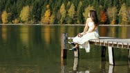 Modern bride lady with sneakers sitting on autumn mountain lake dock Stock Footage