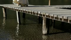 Modern lady feet with sneakers walking on wooden lake pontoon Stock Footage