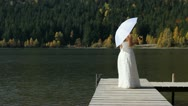 Stock Video Footage of Beutiful bride spinning around on wooden mountain lake pontoon