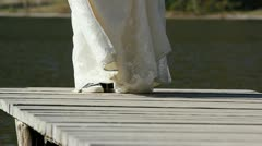 Runaway bride feet waiting on wooden mountain lake pontoon - stock footage