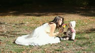 Bride mother and her baby smelling autumn flower bouquet Stock Footage