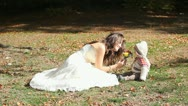 Bride and baby sitting on autumn ground and smelling a flower bouquet Stock Footage
