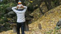Father holding the baby on his shoulders walking in autumn forest - stock footage