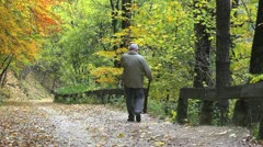 Old man with a rod coming down on autumn alley with colorful leaves Stock Footage
