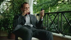 Young businessman with cellphone after hard work drinking whiskey on his balcony Stock Footage
