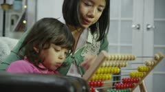Mother teaching her daughter to count with the use of an abacus - stock footage