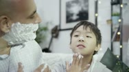 Father teaches his son to apply shaving cream Stock Footage