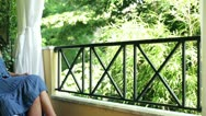 Young woman relaxing on her balcony Stock Footage