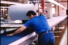 San Francisco, 1970's, giant roll of denim being laid out in layers on long Stock Footage