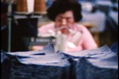 San Francisco, 1970's, follow focus from pile of denim to face of sewer Stock Footage