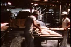 San Francisco, 1970's, Parisian sourdough bakery, brushing tops of loaves Stock Footage