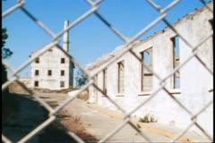 San Francisco, 1970's, Alcatraz prison, building through a chain link fence - stock footage