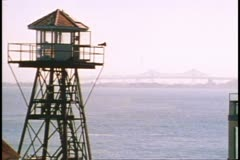 San Francisco, 1970's, Alcatraz prison lighthouse on steel tower, Bay Bridge Stock Footage