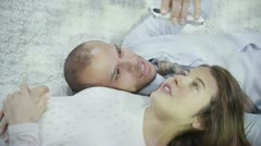 Attractive young couple relaxing and interacting with smart phone - stock footage