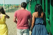 Young group of friends walking on the beach, steadicam shot Stock Footage
