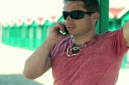 Young man talking on cellphone on the beach, steadicam shot Stock Footage