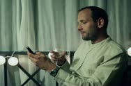 Young man with wine and cellphone relaxing on his balcony in the evening Stock Footage