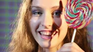 Girl with a lollipop shows different facial expressions Stock Footage